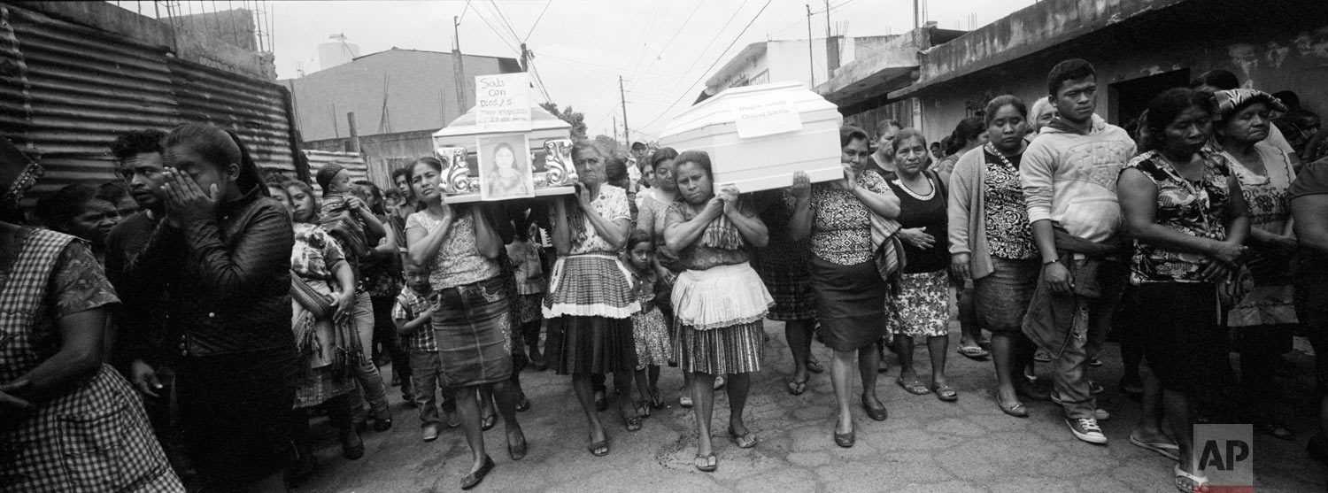 Villagers walk towards the cemetery with the remains of four people who died due to the eruption of the Volcan de Fuego, or Volcano of Fire, on June 10, 2018, in San Juan Alotenango, Guatemala. (AP Photo/Rodrigo Abd)