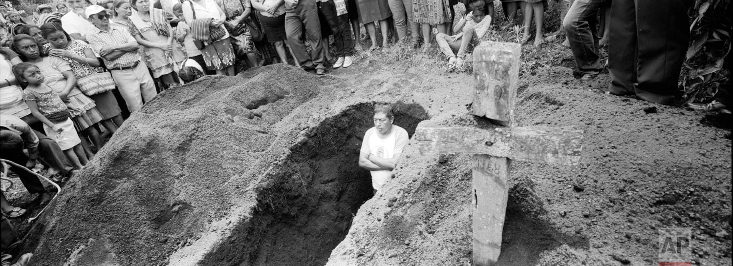 Residents and cemetery workers listen to an evangelical pastor during the burial of 70-year-old Juan Toma Lopez, on June 18, 2018, who died during the eruption of the Volcan de Fuego, or Volcano of Fire, San Juan Alotenango, Guatemala. (AP Photo/Rodrigo Abd)