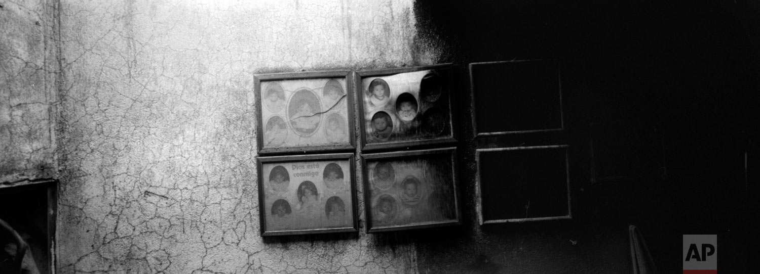 Family portraits burnt by volcanic ash spewed by the Volcan de Fuego or Volcano of Fire hang on the wall of a house on June 8, 2018, in San Miguel Los Lotes, Guatemala. (AP Photo/Rodrigo Abd)