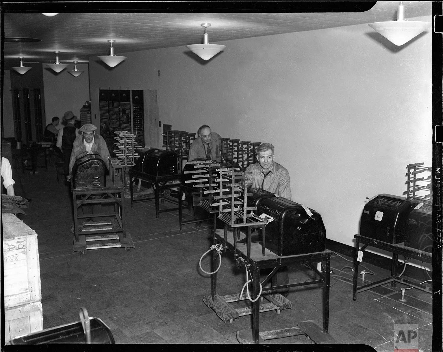 Workmen set up teletype machines in the newsroom at the new Associated Press building at Rockefeller Center, New York. (AP Photo/Corporate Archives)