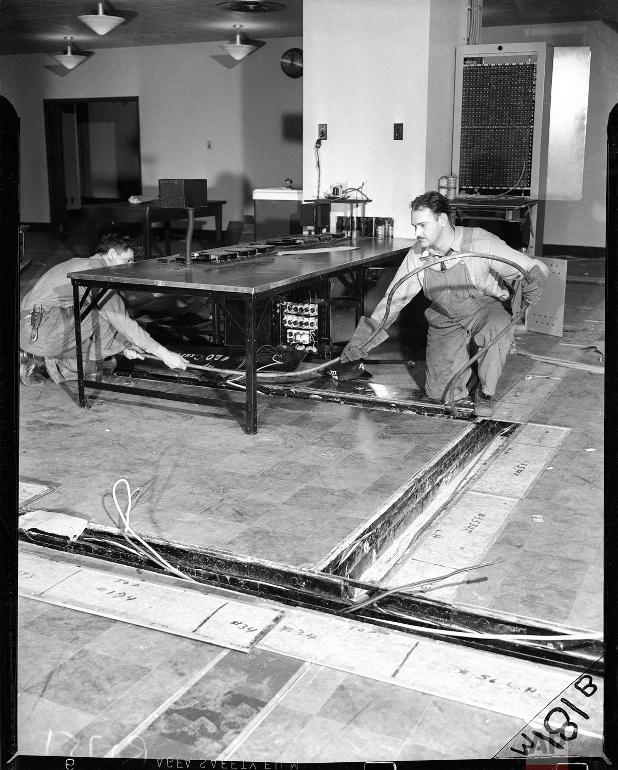 Workers lay cable in floor channels in the market department at Associated Press in the new AP building at Rockefeller Center, New York, in 1938. The market department switchboard and main market operating table are shown.(AP Photo/Corporate Archives)
