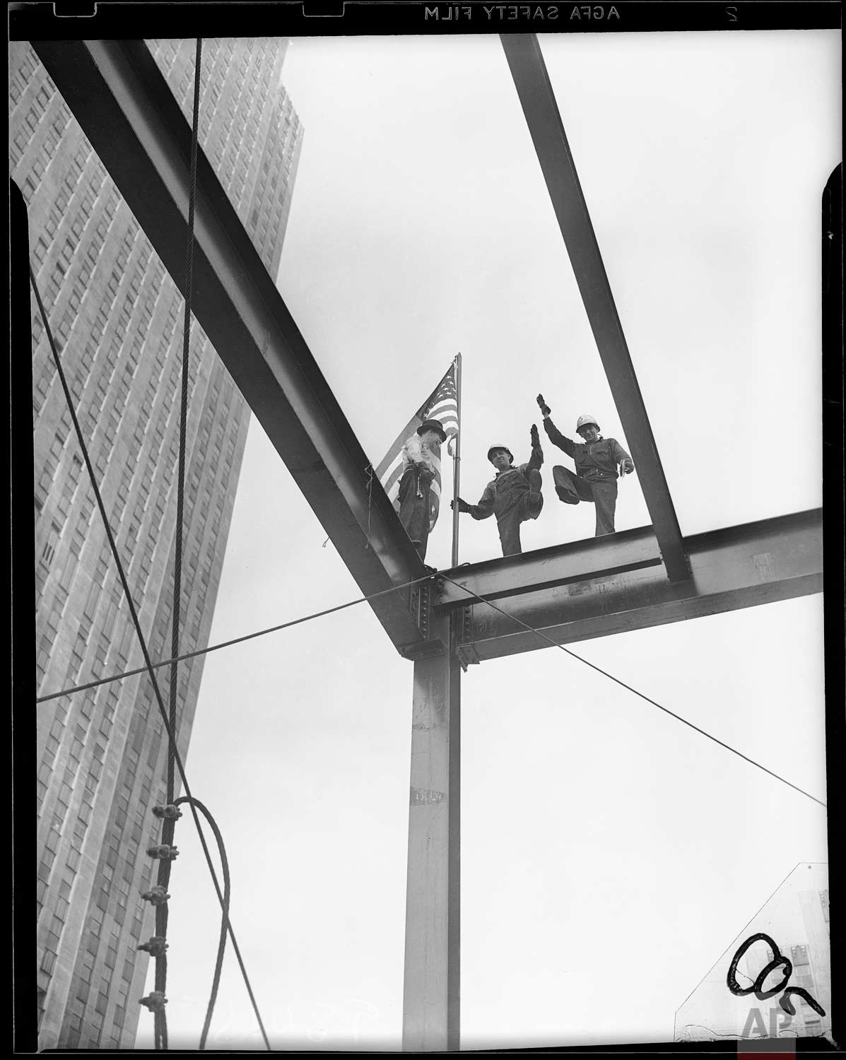 """A """"topping-out"""" ceremony - the raising of an American flag on the topmost girder - marked the completion of the steelwork on the 15-story new Associated Press building at Rockefeller Center, New York, June 16, 1938. (AP Photo/Corporate Archives/Joseph W. Brady)"""