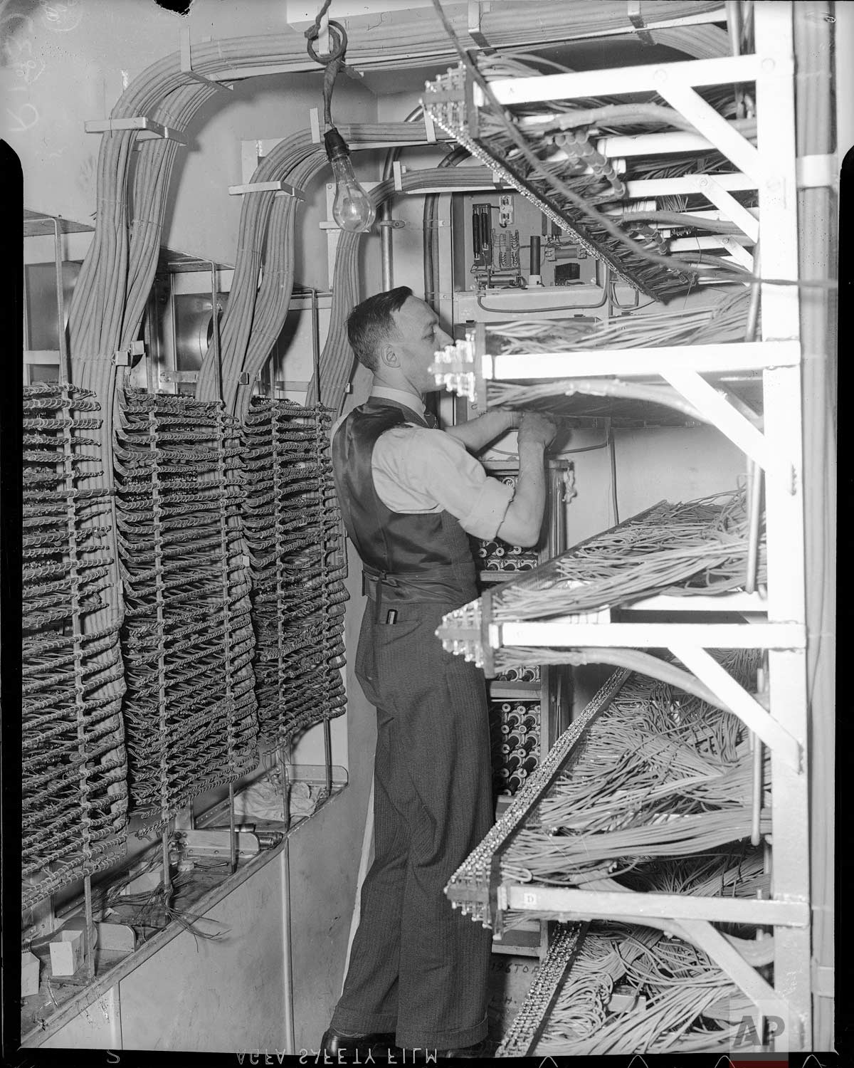 A workman puts finishing touches on the rear of the vast switchboard - nerve center of the worldwide leased wire system of the Associated Press in the new AP building at Rockefeller Center, New York, Dec. 18, 1938. (AP Photo/Corporate Archives)