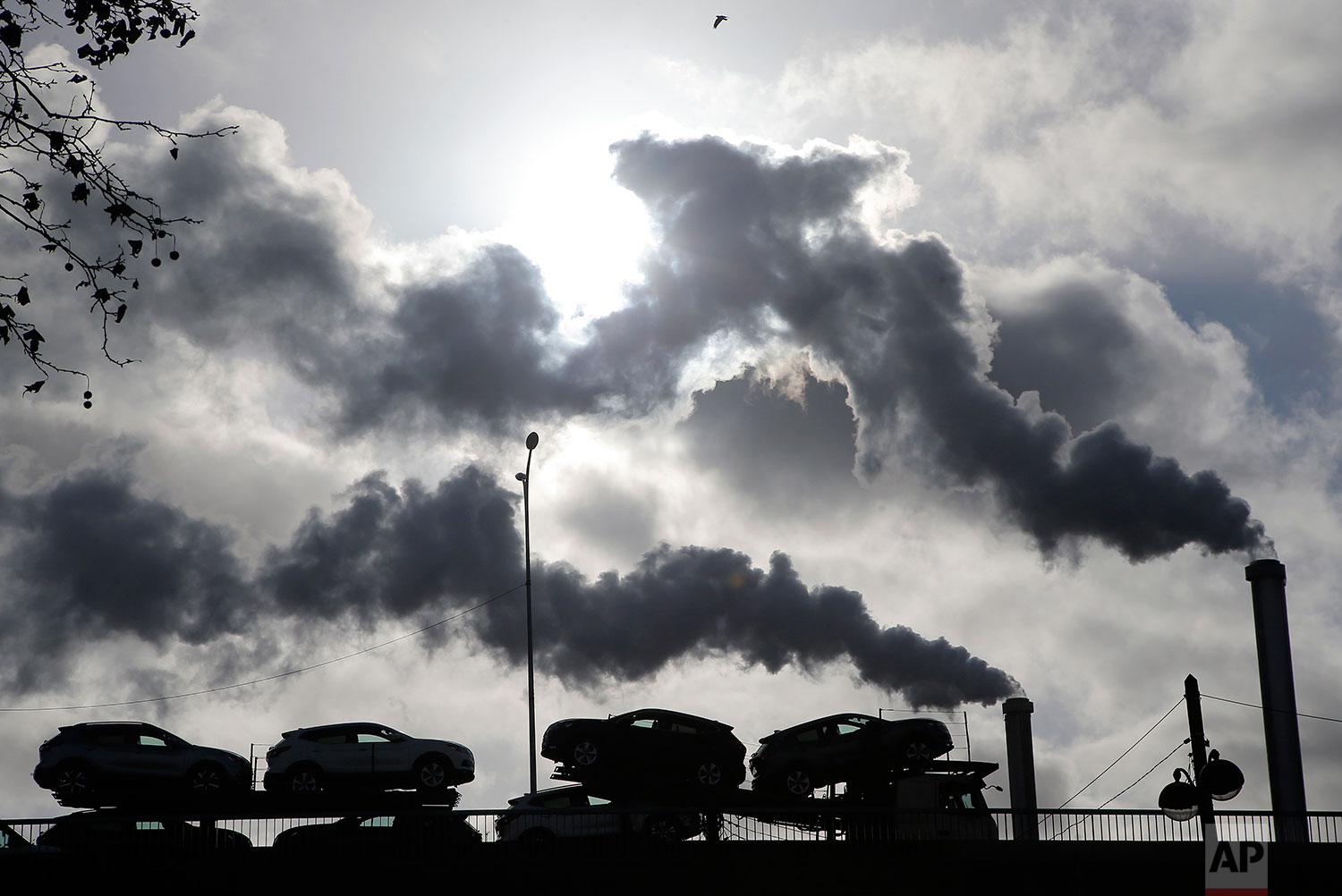 In this Friday, Nov. 30, 2018 photo, smoke rises from a factory as a truck loaded with cars crosses a bridge in Paris, France. (AP Photo/Michel Euler)
