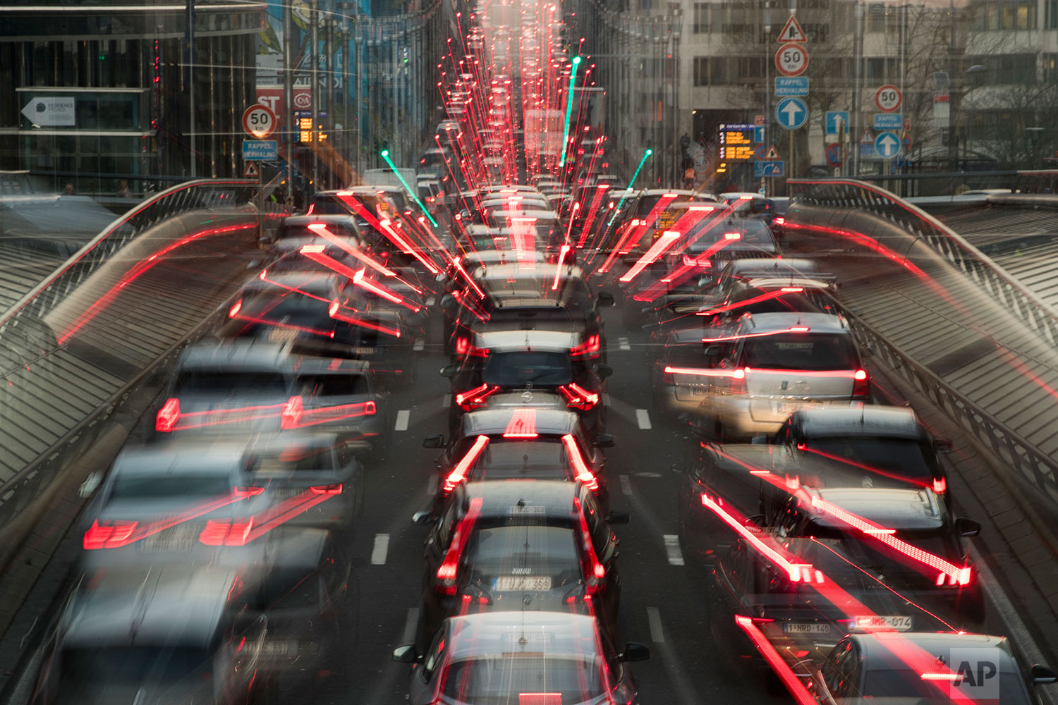 In this slow-shutter zoom effect photo taken on Wednesday, Dec. 12, 2018, commuters are backed up in traffic during the morning rush hour, in Brussels, a city that regularly experiences pollution alert warnings. (AP Photo/Francisco Seco)