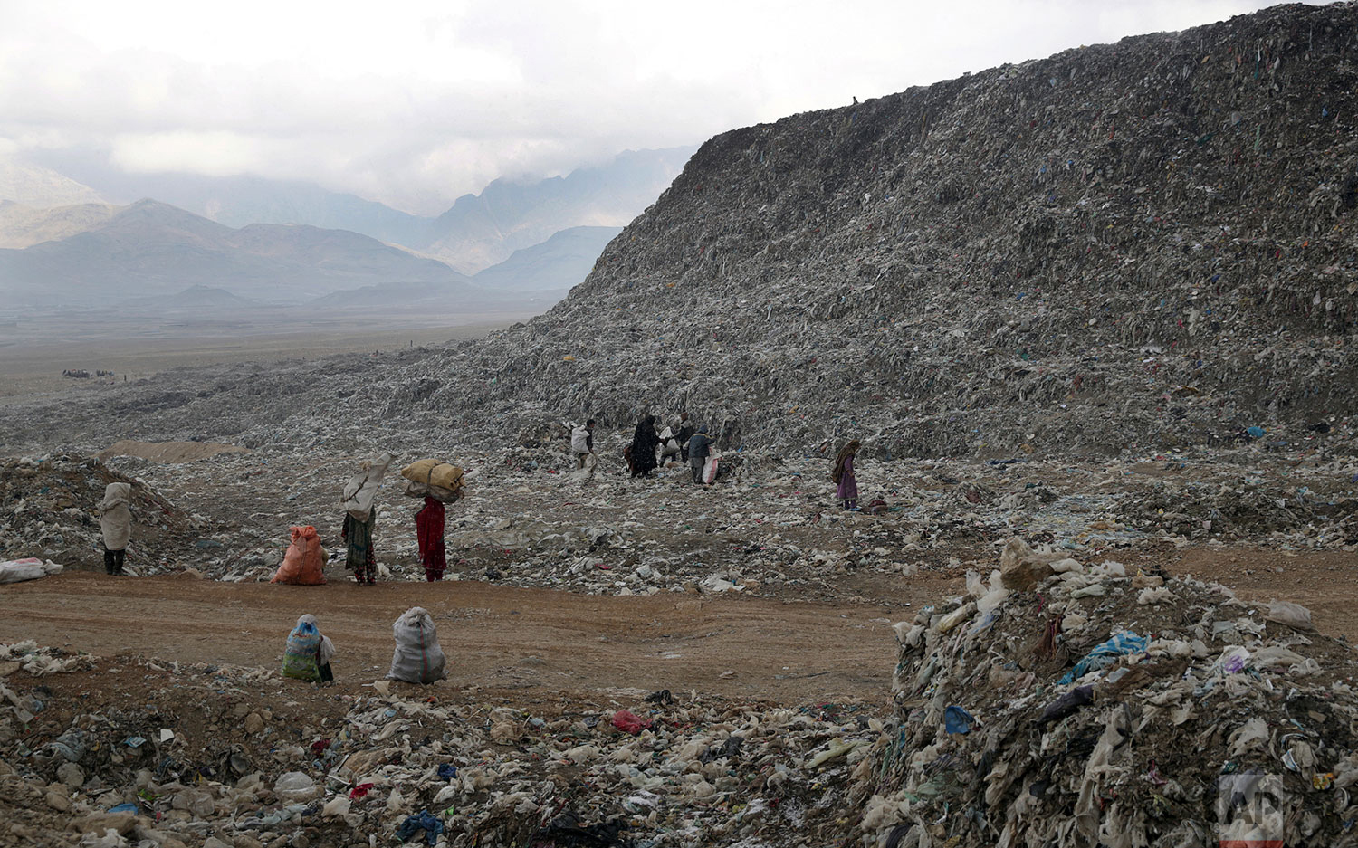 In this Tuesday, Dec. 11, 2018 photo, people, who scavenge recyclable materials from garbage for a living, walk near a mountain of garbage at the dump on the outskirts of Kabul, Afghanistan. (AP Photo/Massoud Hossaini)