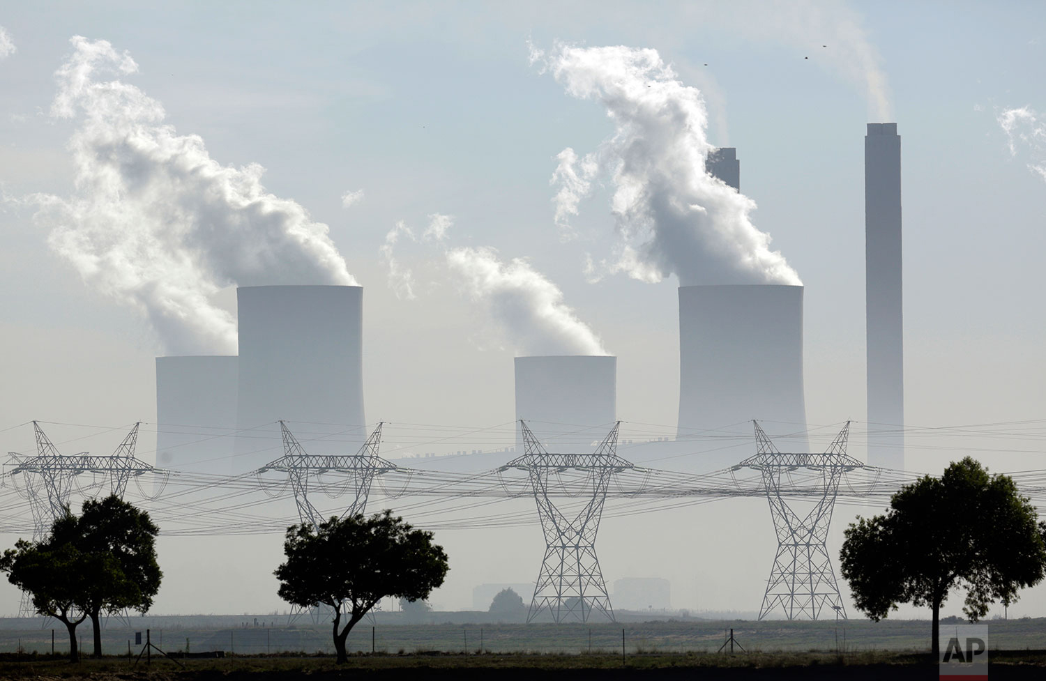 In this Wednesday, Dec. 5, 2018 photo, smoke billows from the chimneys at Lethabo Power Station, a coal fired power station, in Vereeniging, South Africa. (AP Photo/Themba Hadebe)