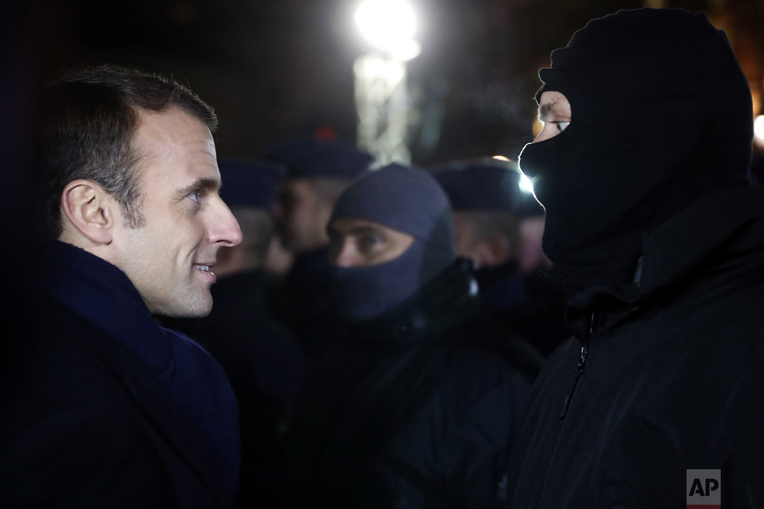 French President Emmanuel Macron meets police officers wearing hoods near the Christmas market in Strasbourg, eastern France, Friday, Dec.14, 2018. A fourth person died Friday from wounds suffered in an attack on the Christmas market in Strasbourg, as investigators worked to establish whether the main suspect had help while on the run. (AP Photo/Jean-Francois Badias, Pool)