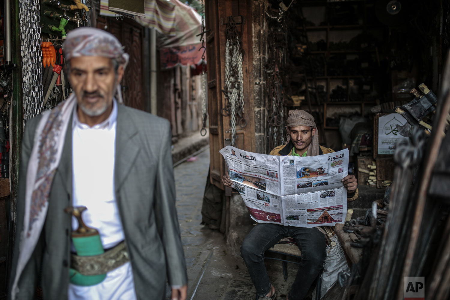 A man reads al-Thawra newspaper at Souq al-Melh marketplace in the old city of Sanaa, Yemen, Tuesday, Dec. 11, 2018. Yemen's warring sides agreed Thursday to an immediate cease-fire in the strategic port city of Hodeida, where fighting has disrupted vital aid deliveries and left the country on the brink of starvation in the 4-year-old civil war. (AP Photo/Hani Mohammed)