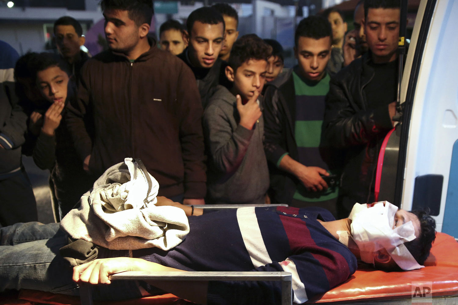 Palestinians watch medics move a wounded youth who was shot by Israeli troops during a protest at the Gaza Strip's border with Israel, into the treatment room of Shifa hospital in Gaza City, Friday, Dec. 14, 2018. Hamas has orchestrated demonstrations on a weekly basis since March, demanding an end to a crippling Israeli-Egyptian blockade on the territory. (AP Photo/Adel Hana)