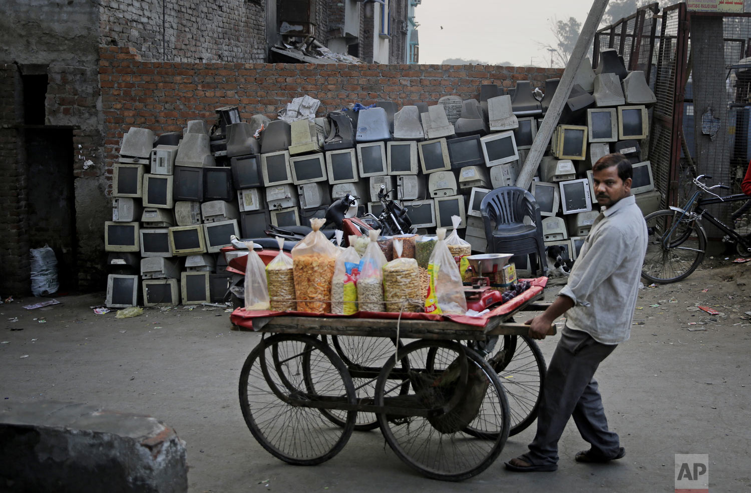 A snack vendor pushes his cart past discarded computer monitors stacked next to a wall on the side of a road in New Delhi, India, on Saturday, Dec. 8, 2018. (AP Photo/Altaf Qadri)