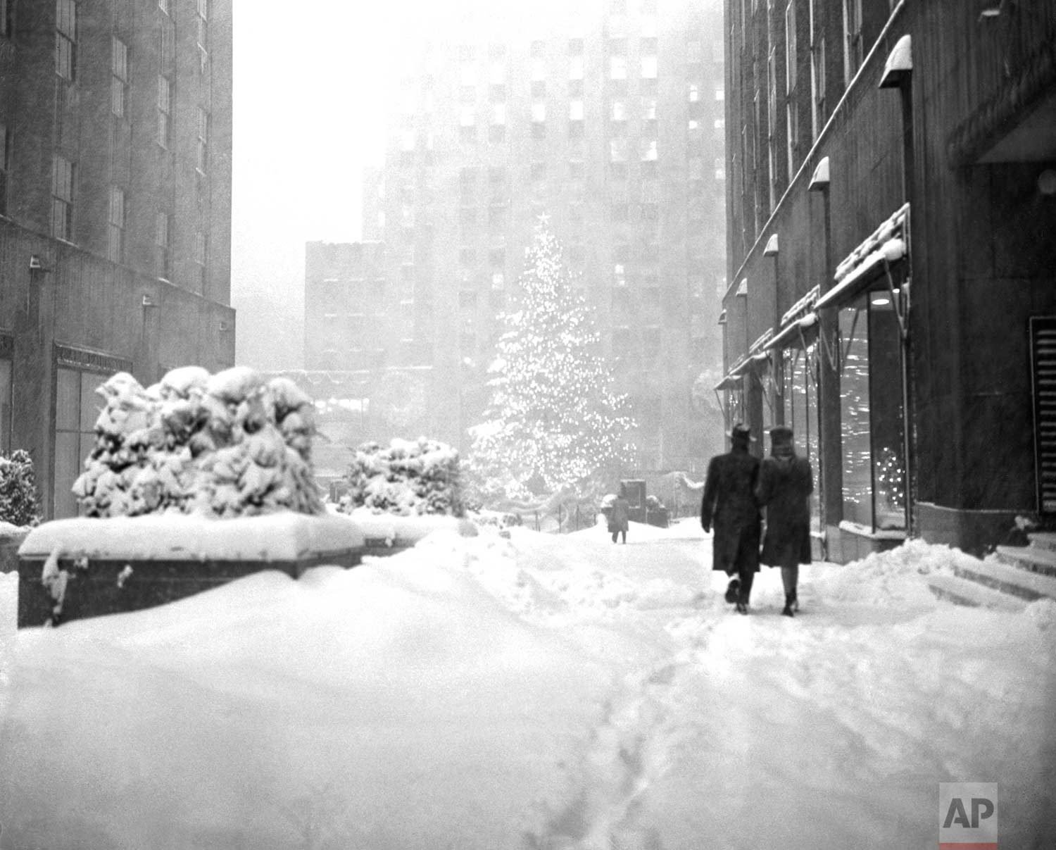 The landmark Christmas tree at New York's Rockefeller Plaza stands out Dec. 26, 1947 as a few hardy pedestrians make their way through the snow drifts of one of the heaviest winter storms in years. (AP Photo/Harry Harris)