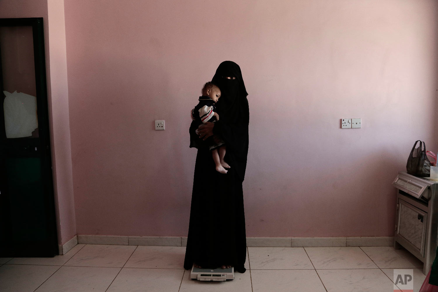 Umm Mizrah, a 25-year-old Yemeni woman, holds her son Mizrah on a scale in Al-Sadaqa Hospital in the southern Yemen city of Aden in this Feb. 13, 2018 photo. The woman, who is nearly into the second trimester of her pregnancy, weighed 38 kilograms (84 pounds), severely underweight. Mizrah, who was 17 months old, weighed 5.8 kilograms (12.8 pounds), around half the normal weight for his age. (AP Photo/Nariman El-Mofty)
