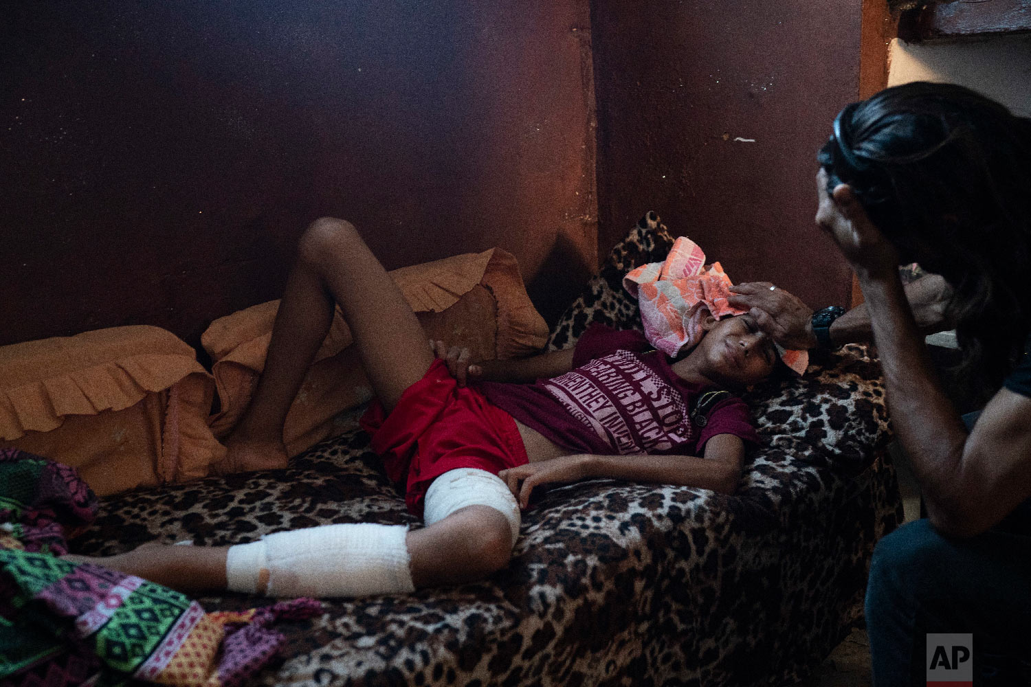 Raed Abu Khader, right, holds a wet cloth on the forehead of his 12-year-old son Mohammed in Gaza City, Sept. 12, 2018. Mohammed was shot in the leg at one of the demonstrations on Gaza strip's border with Israel. (AP Photo/Felipe Dana)