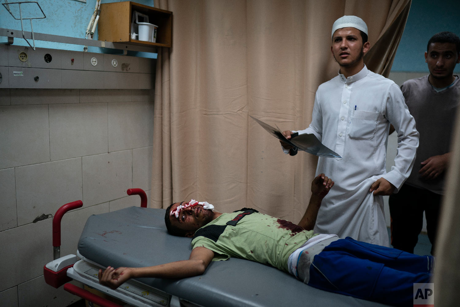 A Palestinian receives medical attention in a hospital after being injured during a protest at the Gaza Strip's border with Israel, east of Gaza City, Sept. 14, 2018. (AP Photo/Felipe Dana)
