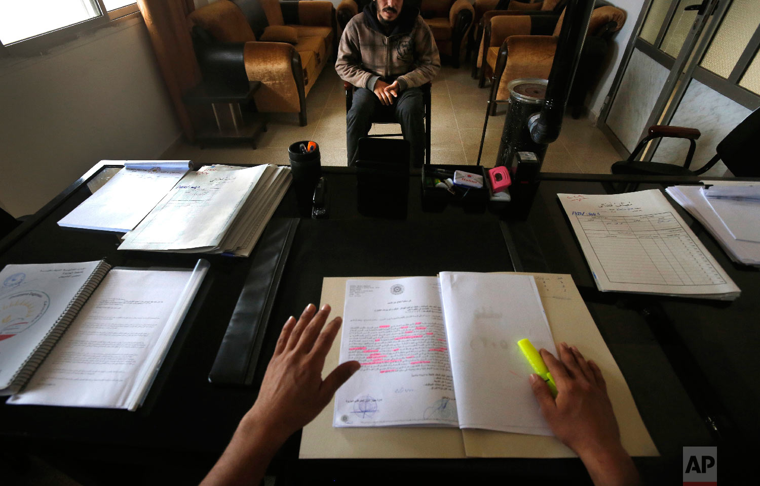 A Syrian 19-year-old former member of the Islamic State group, who declined to be identified, sits opposite a panel of judges in the courtroom of a Kurdish-run terrorism court, in Qamishli, north Syria on April 3, 2018. (AP Photo/Hussein Malla)