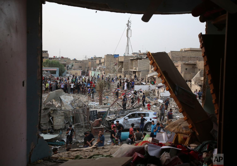 People inspect the scene after blasts in Baghdad's Sadr City, Iraq, Thursday, June 7, 2018. (AP Photo/Karim Kadim)