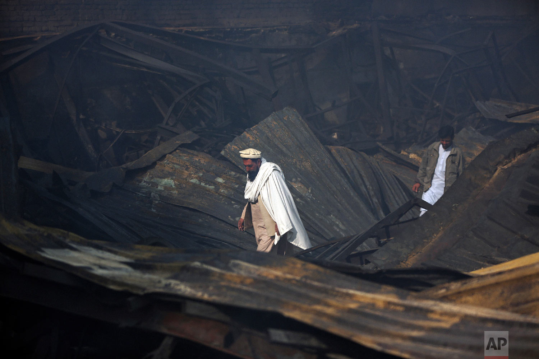 Men walk among the ruins after a fire devastated an electronic appliances market, in Kabul, Afghanistan, Nov. 2, 2018. (AP Photo/Massoud Hossaini)