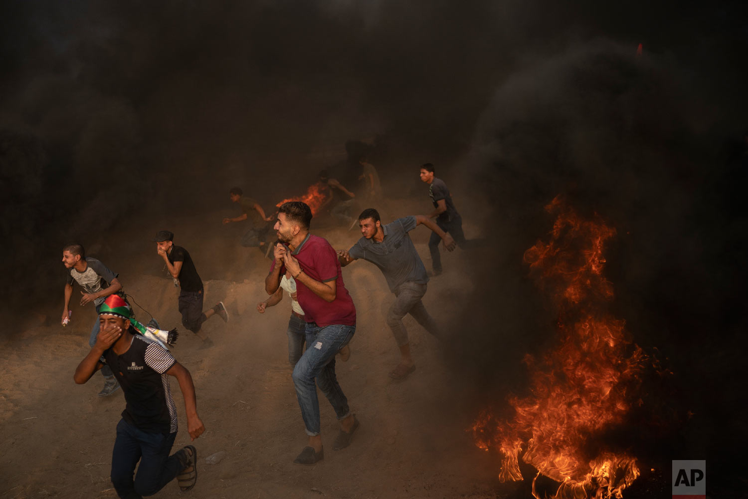 Palestinian protesters run from teargas fired by Israeli troops during a protest at the Gaza Strip's border with Israel, east of Gaza City, Aug. 31, 2018. (AP Photo/Felipe Dana)
