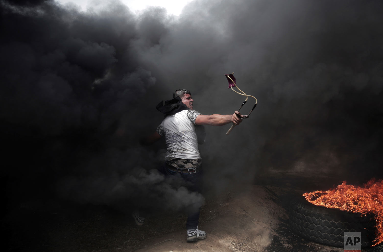 A Palestinian protester hurls stones at Israeli troops during a protest at the Gaza Strip's border with Israel, Friday, April 20, 2018.(AP Photo/ Khalil Hamra)