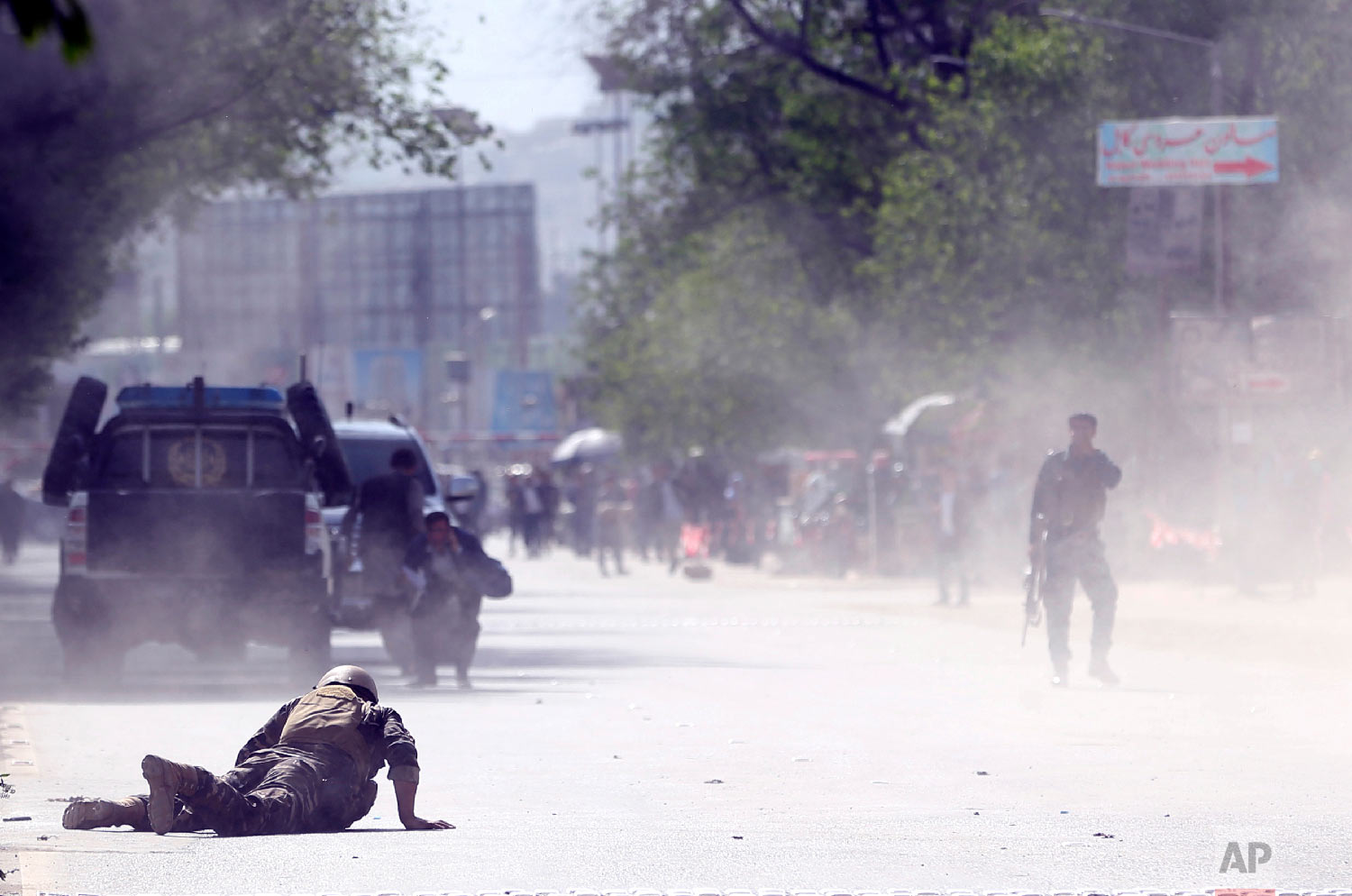 A soldier and a civilian lie low at the site of a suicide attack after the second bombing in Kabul, Afghanistan, April 30, 2018. (AP Photo/Massoud Hossaini)