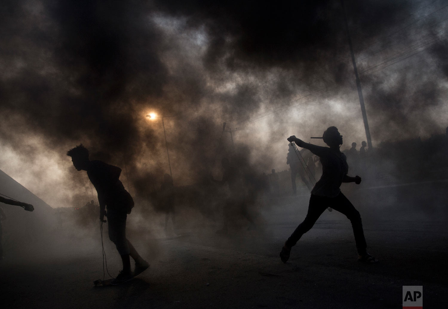 Palestinian protesters hurl stones during a demonstration at the entrance of Erez border crossing between Gaza and Israel, in the northern Gaza Strip, Oct. 3, 2018. (AP Photo/Khalil Hamra)