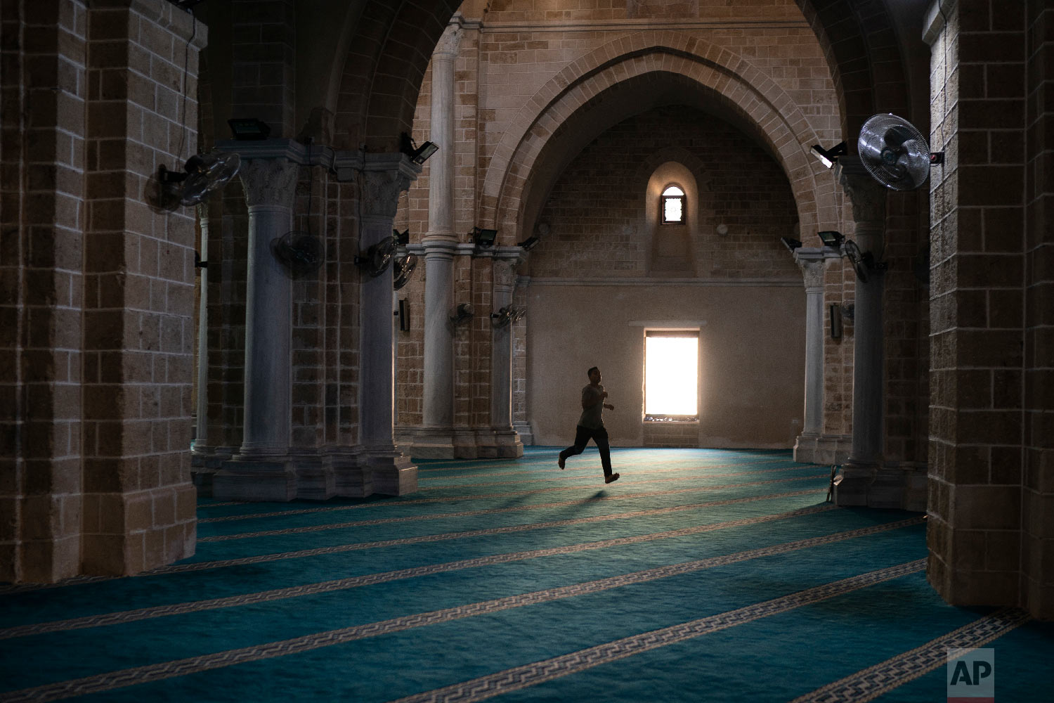 A man runs as he arrives a few minutes late for the afternoon prayer in a mosque in Gaza City, Sept. 14, 2018. (AP Photo/Felipe Dana)