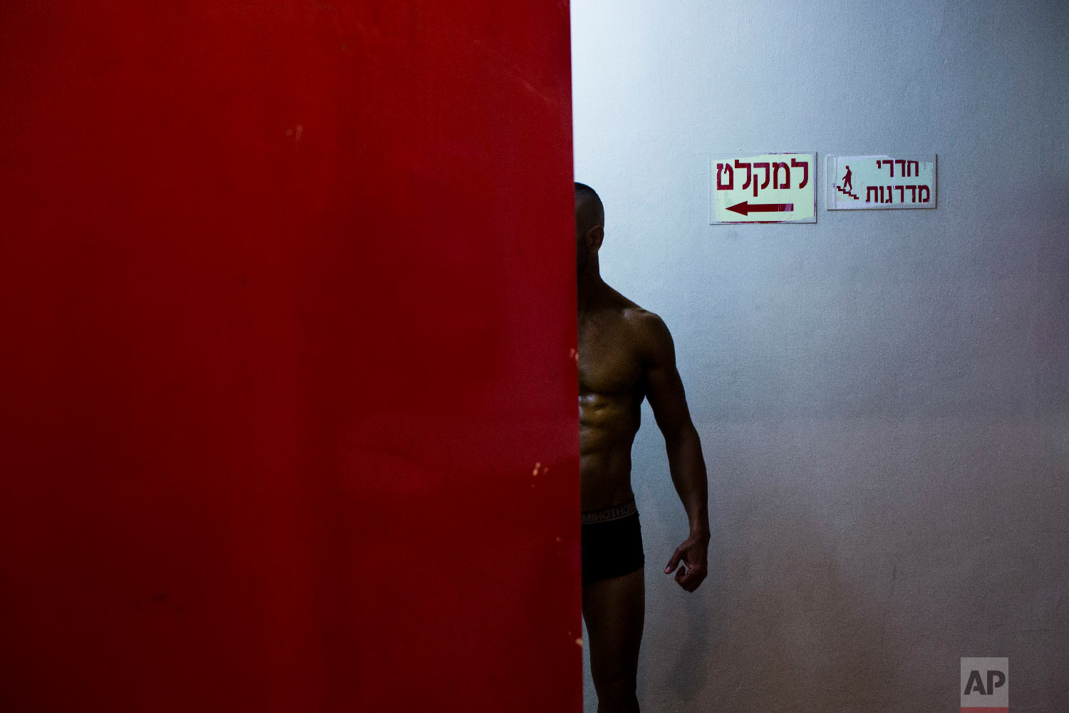 A contestant has his body painted backstage during the National Amateur Body Builders' Association competition in Tel Aviv, Israel, Oct. 18, 2018. (AP Photo/Oded Balilty)
