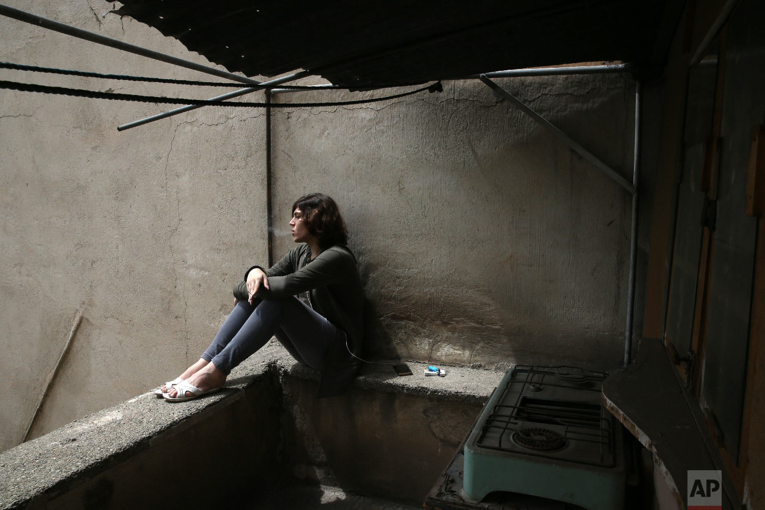Nahal, a 19-year-old transgender woman smokes cigarette on her balcony in Tehran, Iran, April 22, 2018. Nahal had hardly started high school before being forced to leave over her classmates' instance she dress as a man. Her manicured fingernails, painted pink, brush away her long brown hair as she looks through old photographs of her childhood, recounting how even her own family has struggled to accept her. (AP Photo/Vahid Salemi)