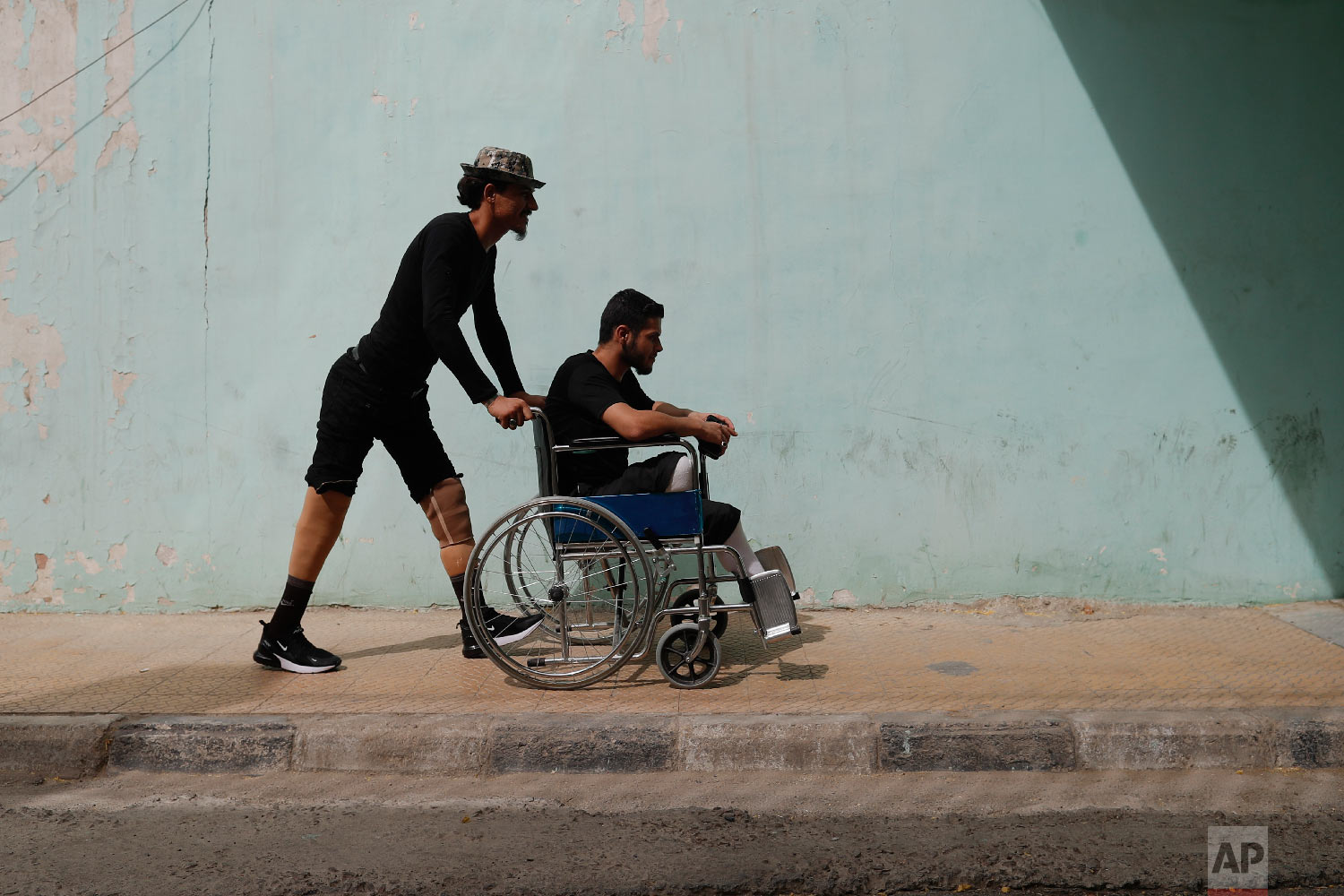 A Syrian soldier who lost his legs while fighting in Syria's war, helps his comrade after a physical therapy session, at the Ahmad Hamish Martyr hospital in Damascus, Syria, Oct. 7, 2018. (AP Photo/Hassan Ammar)