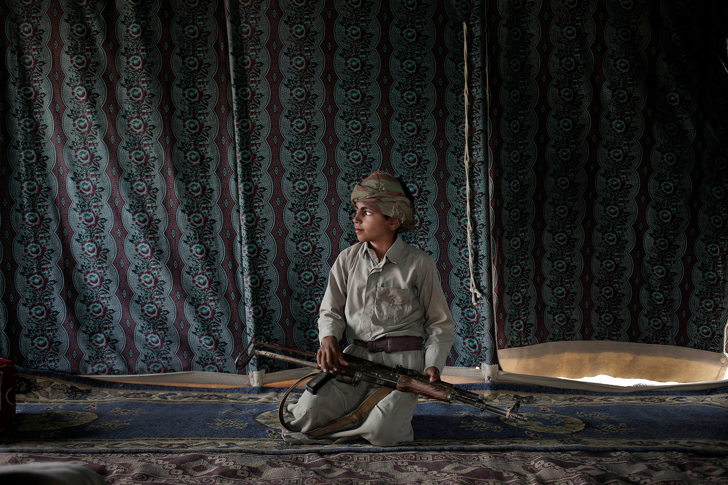 In this July 27, 2018 photo, 12 year-old Kahlan Sales Amer, demonstrates how to use a rifle, at a camp for displaced persons where he took shelter with his family, in Marib, Yemen, (AP Photo/Nariman El-Mofty)