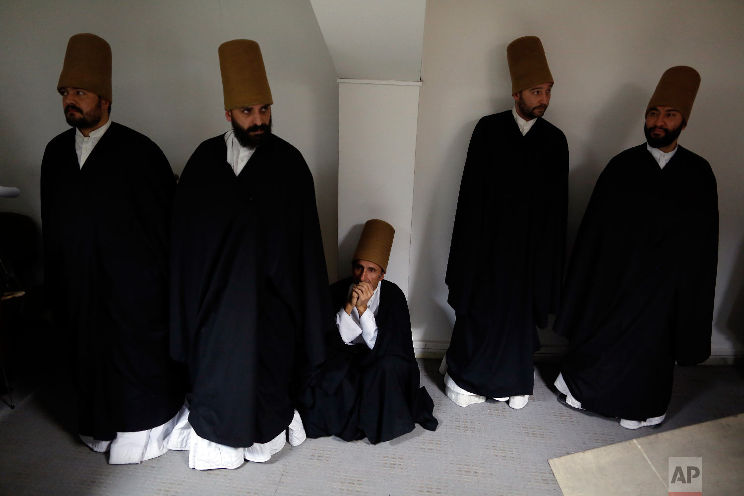 Whirling dervishes of the Mevlevi order wait to perform at a Sheb-i Arus ceremony in Konya, central Turkey, Sunday, Dec. 16, 2018. (AP Photo/Lefteris Pitarakis)