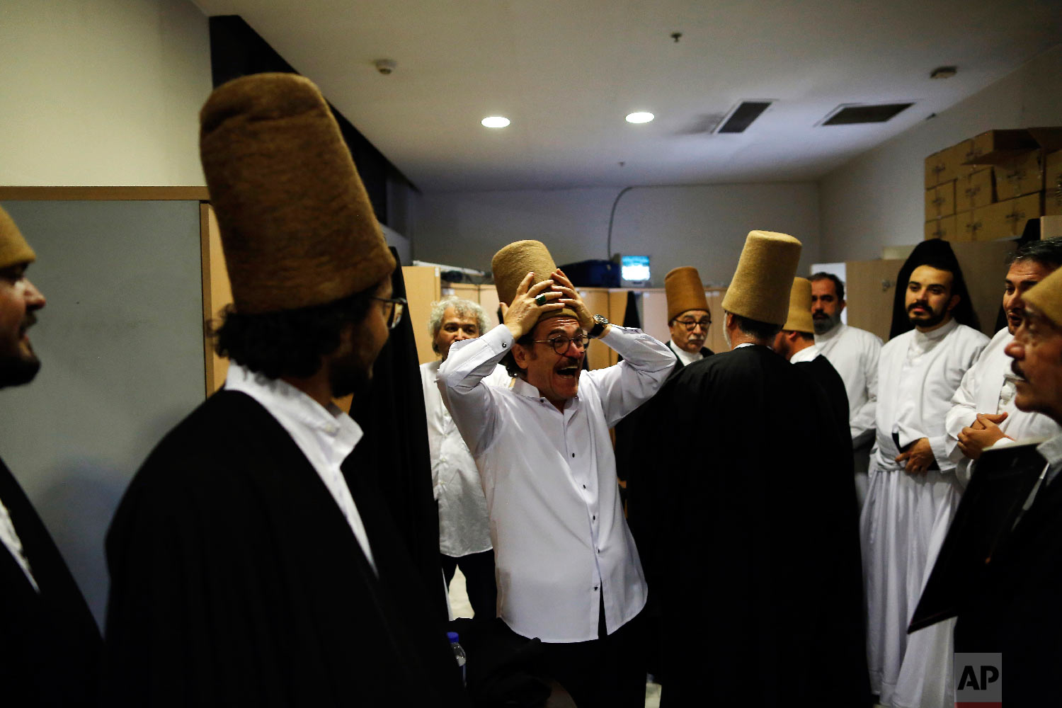 Whirling dervishes of the Mevlevi order enjoy a light moment in the locker room prior to a Sheb-i Arus ceremony in Konya, central Turkey, Sunday, Dec. 16, 2018. (AP Photo/Lefteris Pitarakis)