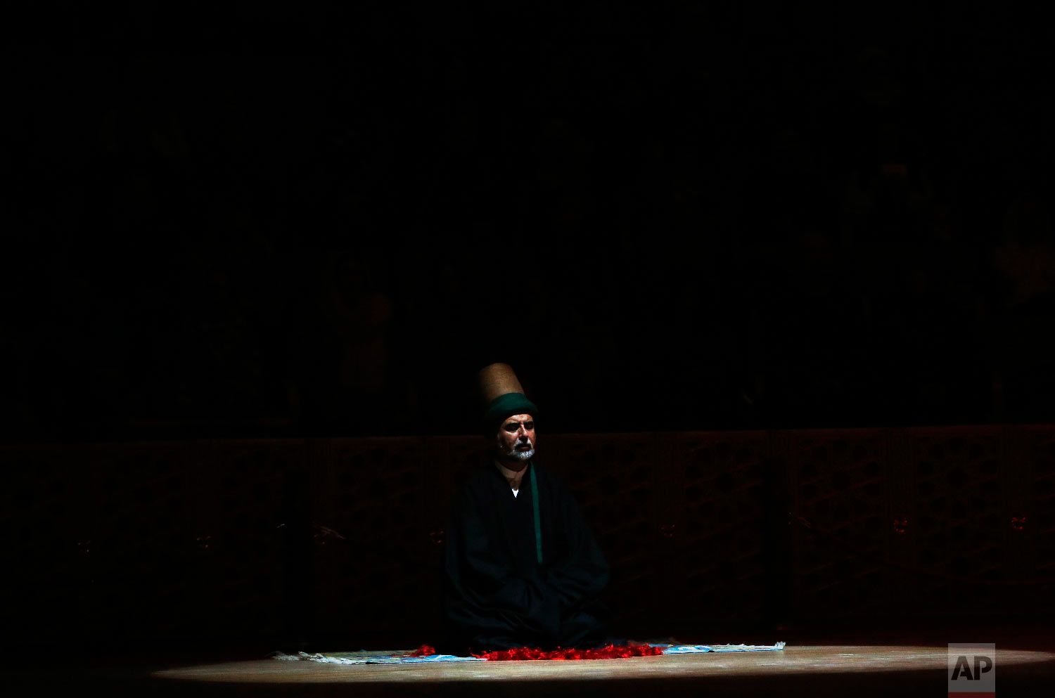 A sheikh of the Mevlevi order of whirling dervishes offers his prayers during a Sheb-i Arus ceremony in Konya, central Turkey, Sunday, Dec. 16, 2018. (AP Photo/Lefteris Pitarakis)