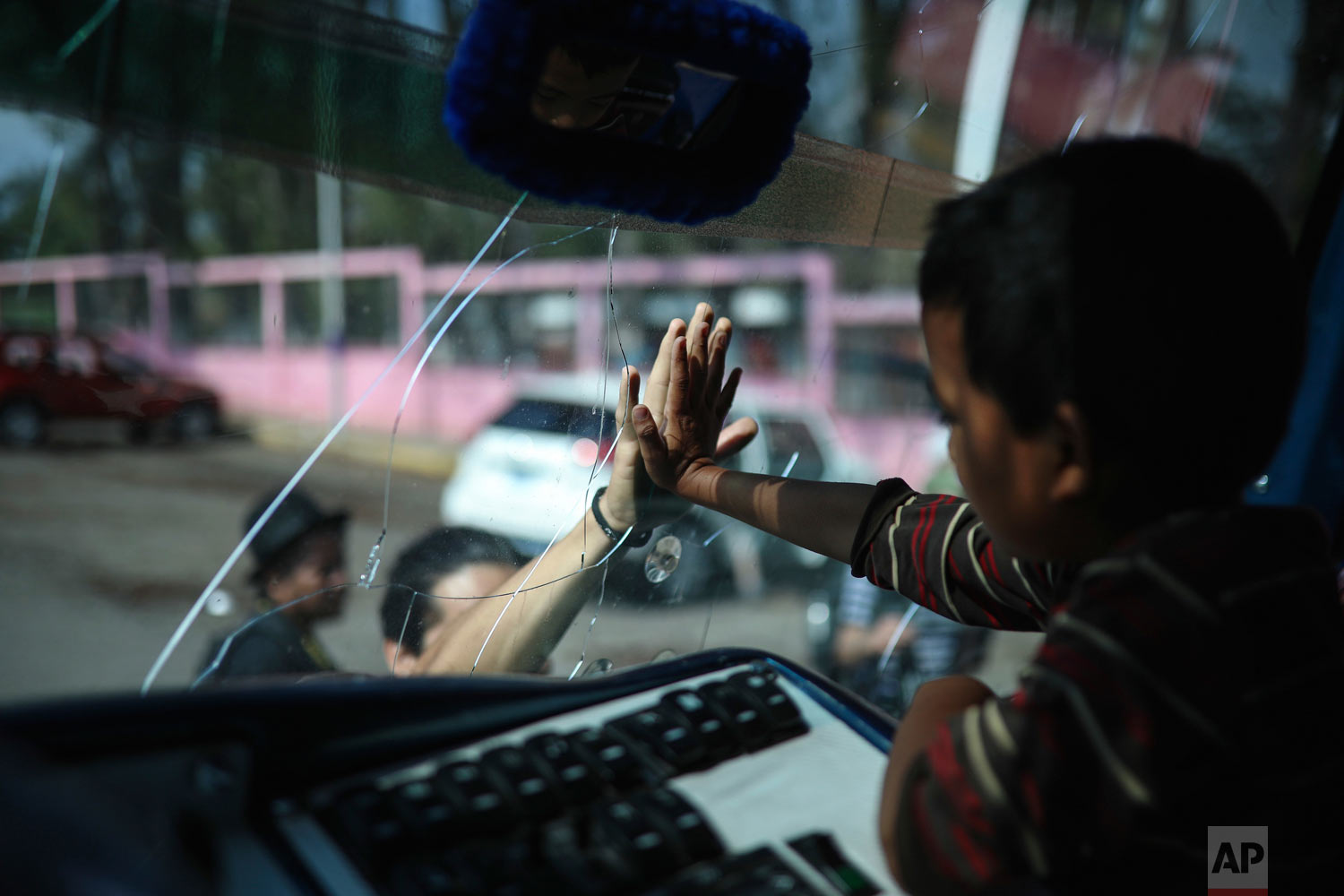 "In this April 5, 2018 photo, a migrant says goodbye to a friend through the windshield of a bus that will carry him to the capital from Matias Romero, Oaxaca state, Mexico where Central American migrants with the annual ""Stations of the Cross"" caravan camped out. The Easter-season caravans have been held annually for about 10 years to draw attention to the plight of migrants, but was never equipped to march all the way to the US. (AP Photo/Felix Marquez)"