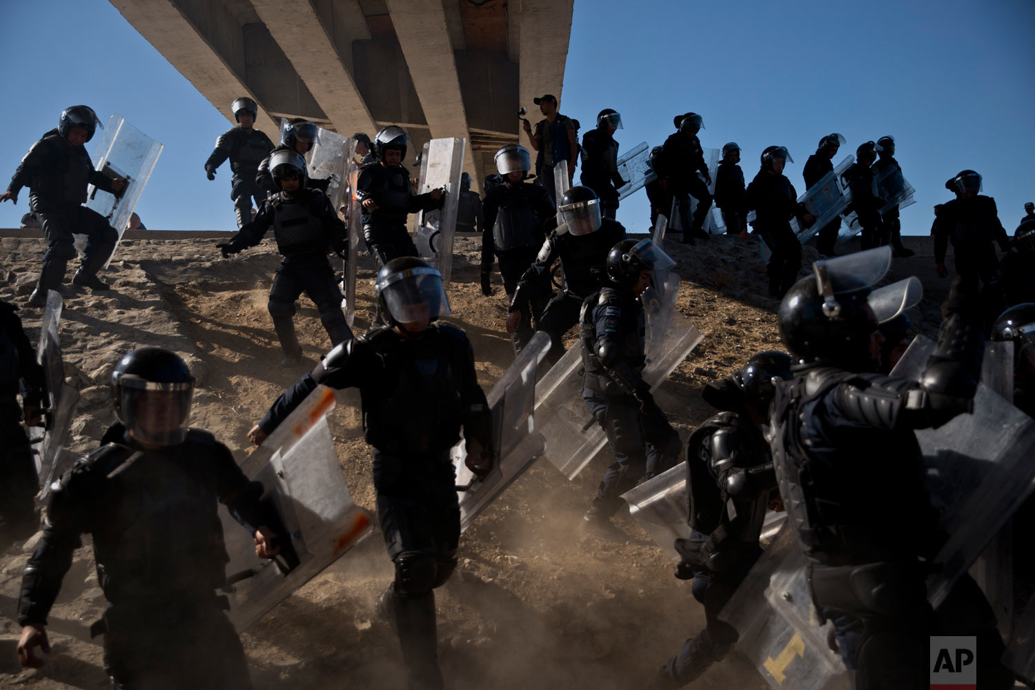 In this Nov. 25, 2018 photo, Mexican police try to keep Central American migrants from getting past the border crossing in Tijuana, Mexico. The mayor of Tijuana declared a humanitarian crisis in his city and said he asked the U.N. for aid to deal with the approximately 5,000 Central American migrants who arrived in caravans. (AP Photo/Ramon Espinosa)