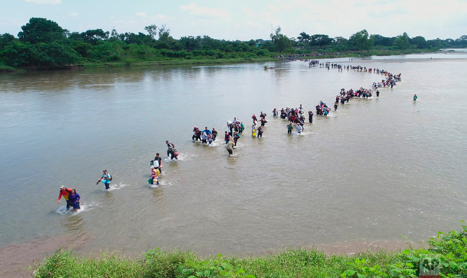 In this Nov. 2, 2018 photo, migrants from El Salvador traveling in a caravan cross the Suchiate River, the border between Guatemala and Mexico, after Mexican authorities told them at the border crossing that they would have to show passports and visas in groups of 50 for processing. Afraid they'd be deported, they waded across the river to enter Mexico. (AP Photo/Oscar Rivera)