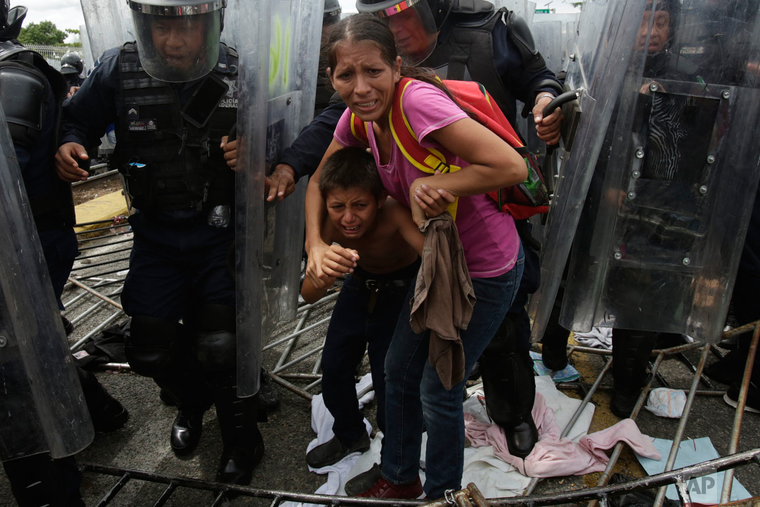In this Oct. 19, 2018 photo, a Honduran migrant mother and child are shielded by Mexican federal police from stones thrown by unidentified people as a caravan of migrants tries to cross the Guatemalan border to Ciudad Hidalgo, Mexico. The mother and child were unsuccessful in their attempt to cross into Mexico and were returned to the Guatemalan side. (AP Photo/Moises Castillo)