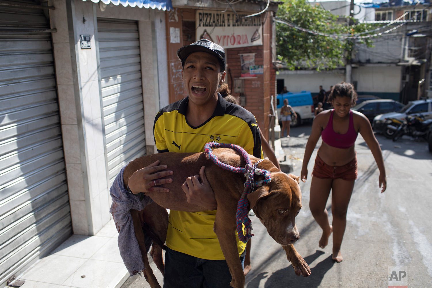 In this Jan. 25, 2018, photo, a youth carries his dog Thales who was hit by a stray bullet during a heavy exchange of gunfire between police and alleged drug traffickers in the Rocinha slum of Rio de Janeiro, Brazil. The military was put in charge of security in Rio de Janeiro state this year, but critics argue the intervention has targeted poor people and done nothing to address underlying issues like unemployment and income inequality. (AP Photo/Leo Correa)