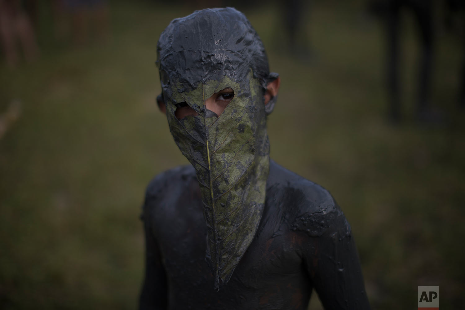 In this Feb. 10, 2018 photo, a mud covered youth poses in his leaf mask during the Mud Block carnival party in Paraty, Brazil. Revelers wrestled, tackled and threw chunks of gunk at each other while dancing to samba and reggaeton at the beach party where clothes were optional but the mud was not. (AP Photo/Leo Correa)
