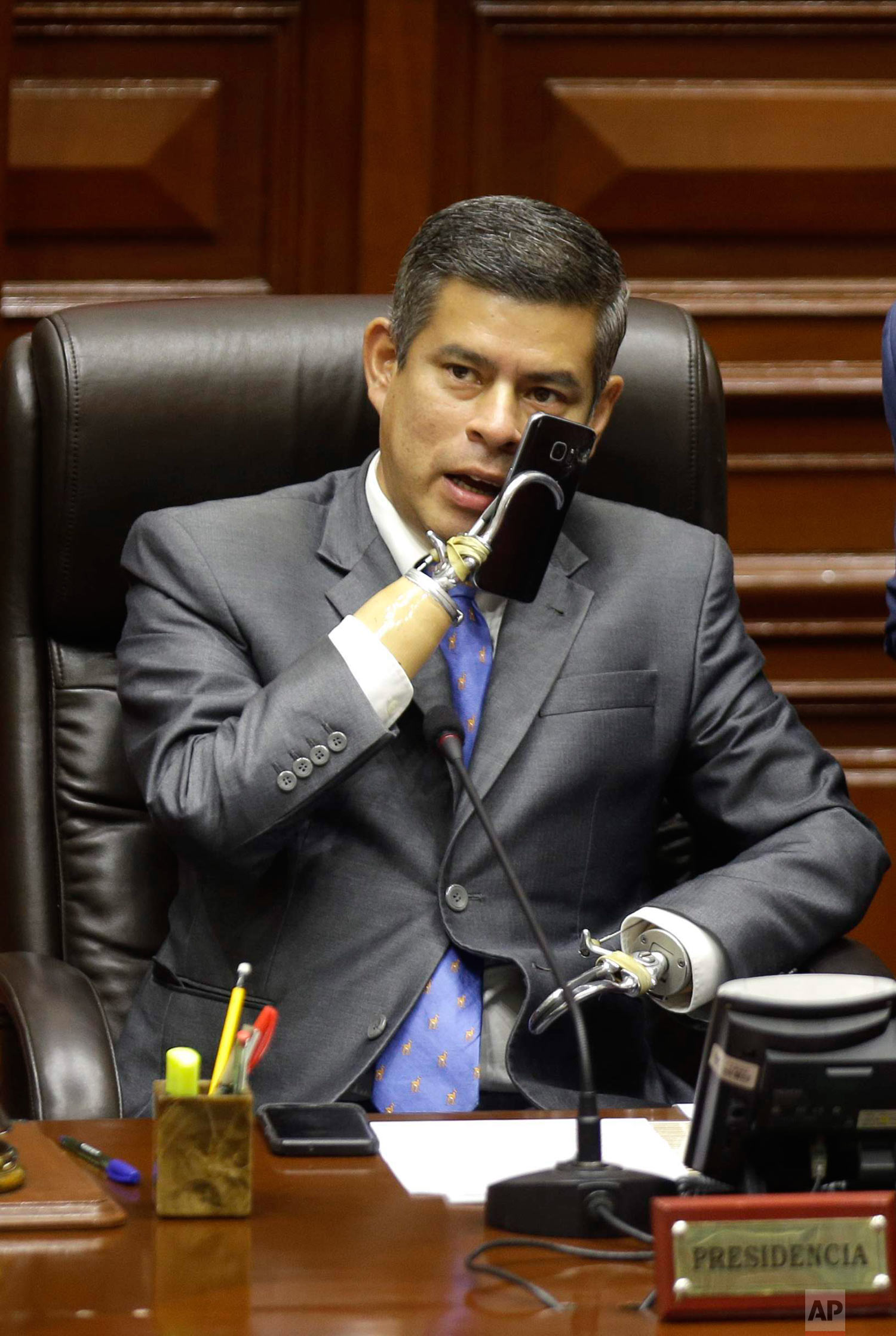 In this March 22, 2018 photo, Congress President Luis Galarreta, who was born without arms, speaks on his cell before the start of a debate on the resignation of Peru's President Pedro Pablo Kuczynski in Lima, Peru. Kuczynski offered his resignation ahead of the impeachment vote, after damaging leaks of confidential documents raised doubts about his integrity and made it impossible to govern. (AP Photo/Martin Mejia)