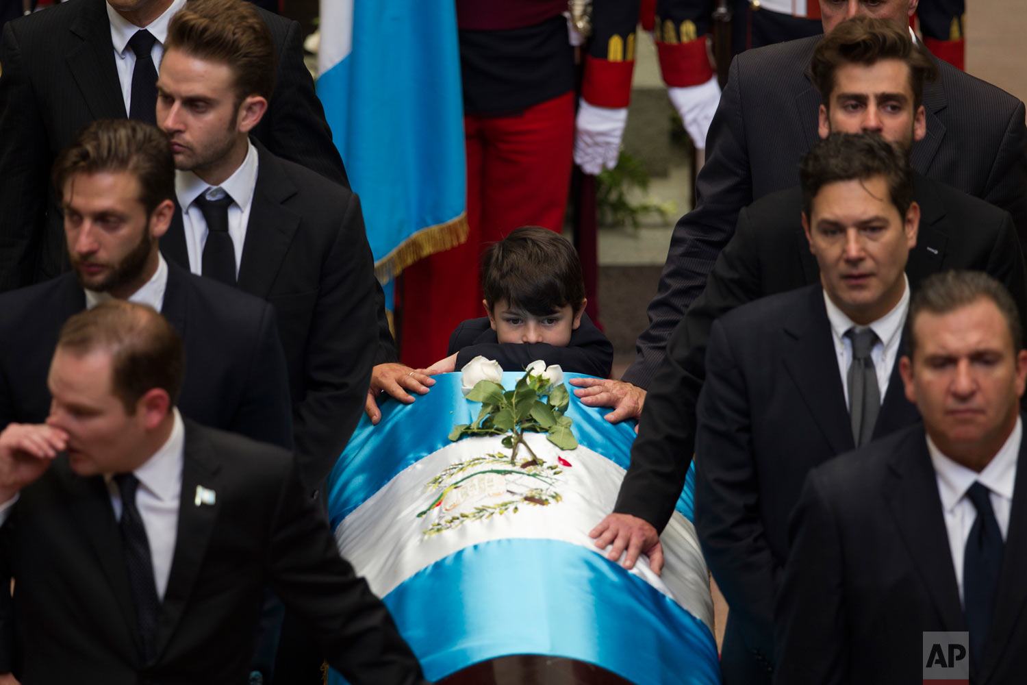 In this April 28, 2018 photo, the coffin of Guatemala's former president and current mayor, Alvaro Arzu, who signed Guatemala's post-civil war peace agreement in 1996, is escorted by relatives at the National Palace in Guatemala City. Arzu died of a heart attack. (AP Photo/Moises Castillo)