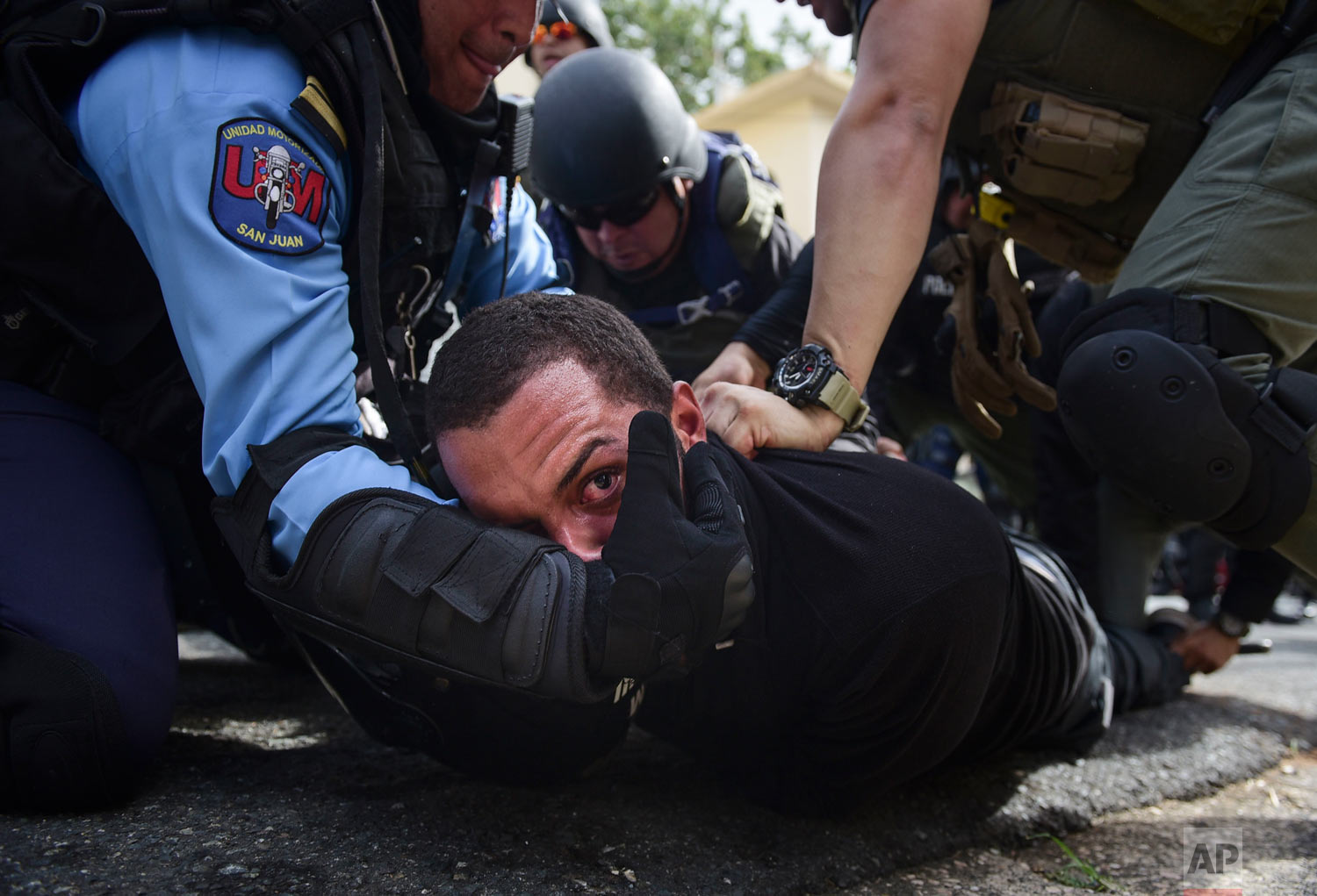 In this May 1, 2018 photo, police detain a protester after a May Day march where people protested pension cuts, school closures and slow hurricane recovery efforts in San Juan, Puerto Rico. Puerto Rico is struggling to emerge from a 12-year-old recession. (AP Photo/Carlos Giusti)