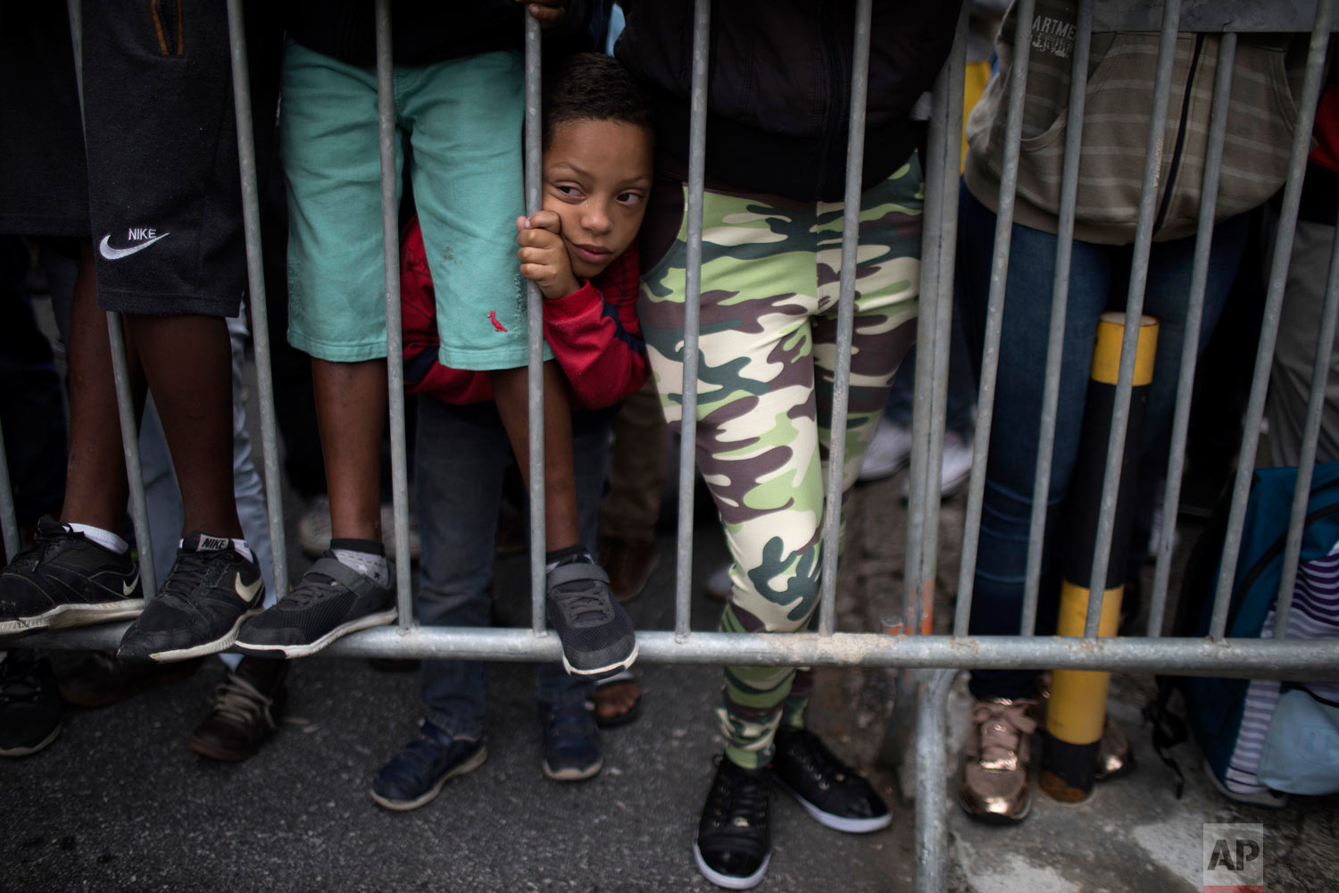 In this May 23, 2018 photo, a boy squeezes between people's legs as he waits outside the Granja Comary training center for a chance to see Brazil's national soccer team in Teresopolis, Brazil. (AP Photo/Leo Correa)