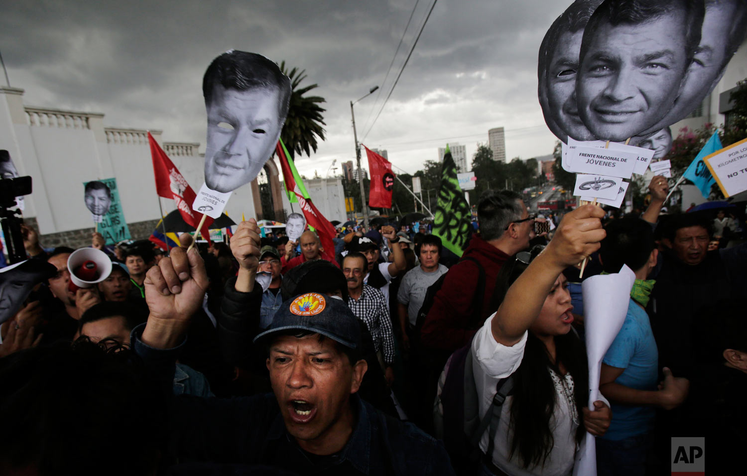 In this June 14, 2018 photo, supporters of Ecuador's former President Rafael Correa hold up images of his face to protest an attempt to prosecute him, outside the National Assembly in Quito, Ecuador. Correa has denied the allegation that he ordered the 2012 kidnapping of political rival Fernando Balda, saying it is part of a campaign by the current government to discredit him and destroy his leftist movement. (AP Photo/Dolores Ochoa)
