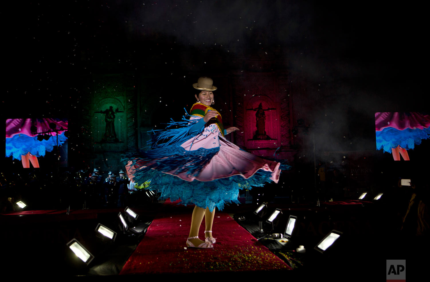 In this June 29, 2018 photo, a woman turns on the catwalk during the Miss Cholita beauty pageant in La Paz, Bolivia. Aymara women participated in the contest that recognizes indigenous women's fashion and beauty as well as their command of indigenous lifestyle and language. (AP Photo/Juan Karita)
