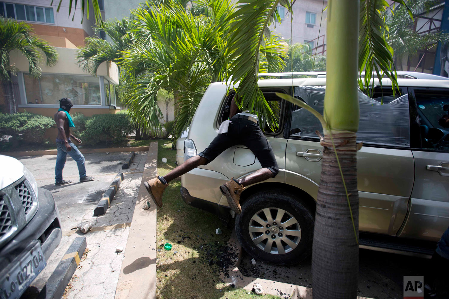 In this July 7, 2018 photo, a man looks inside a car before setting it on fire at the Royal Oasis hotel during protests over a fuel price increase in Port-au-Prince, Haiti. The government announced an increase in prices for gasoline, diesel and kerosene, part of a plan endorsed by the IMF to modernize the economy, but then cancelled the hike after violent protests broke out. (AP Photo/Dieu Nalio Chery)