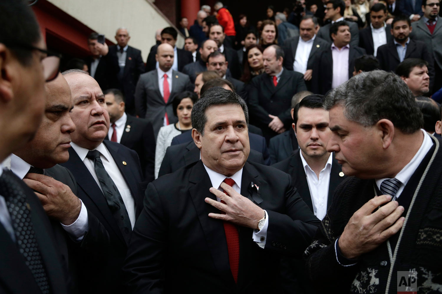 In this July 27, 2018 photo, Paraguay's President Horacio Cartes straightens his tie as he waits for the arrival of the coffin of his Agriculture Minister Luis Gneiting for a memorial service in Asuncion, Paraguay. The minister and three other people died when the twin-engine plane they were traveling in went down shortly after taking off at night. (AP Photo/Jorge Saenz)