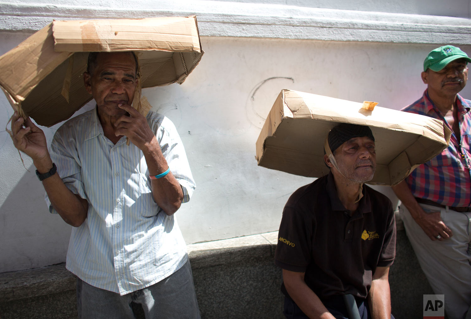 In this Aug. 3, 2018 photo, men shade themselves with cardboard boxes as they wait in line for a vehicle census, a first step to regulate the sale of gasoline, in Caracas, Venezuela. President Nicolas Maduro said that some of the world's cheapest gasoline that Venezuelan drivers enjoy will soon be sold at world market prices, but that those showing their government-issued identification card at the pump will still be able to buy subsidized gasoline. (AP Photo/Ariana Cubillos)