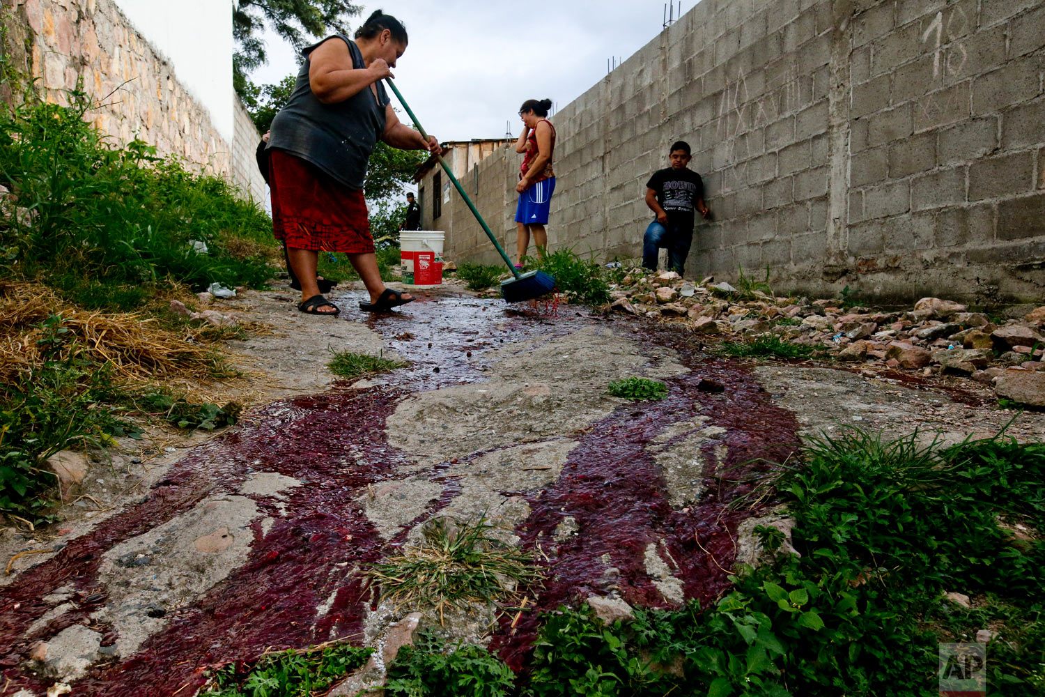 In this Aug. 2, 2018 photo, family members of slain Ronald Blanco try to clean his blood from the alleyway of the Japon neighborhood where the Barrio 18 gang operates Tegucigalpa, Honduras. Family members sprinkled holy water and prayed at the site before working to wash away the blood stains, as passing neighbors gave them their condolences. (AP Photo/Esteban Felix)